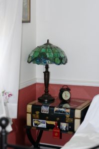 I've had this old suitcase since college.  A bit smelly so not very useful.  I found this luggage stand at The People's Store in Lambertville NJ, and it made the most fantastic side table!  The lamp is a reproduction from overstock.com, the shade is acrylic but very passable as real glass until you touch it.